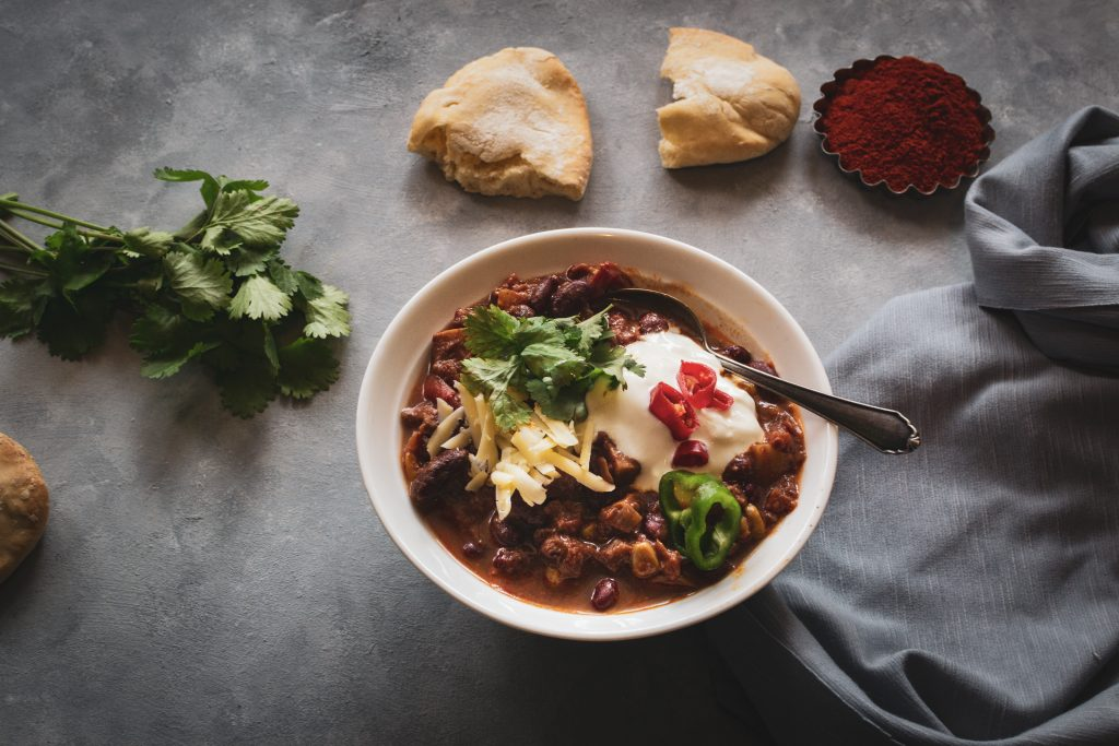 45˚ photo of a bowl of chilli topped with sour cream and cheese and served with pitta and fresh coriander with a grey background