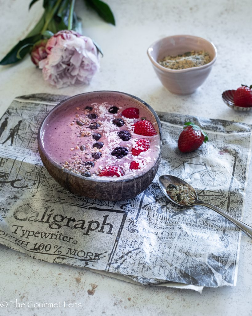Close up of pink pityaya smoothie bowl with berries and sprinkled coconut and seeds on an old newspaper with peonies
