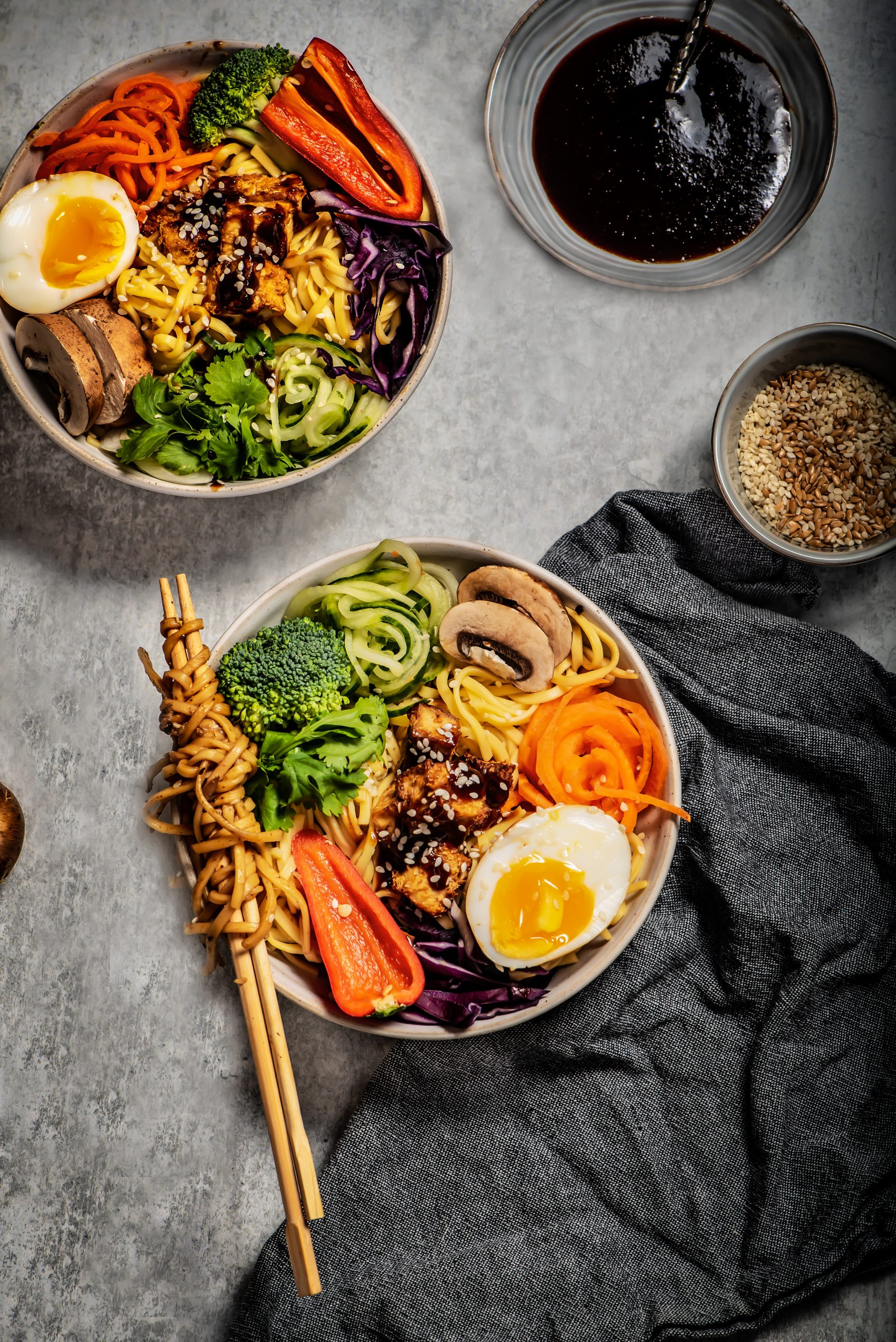 Flatlay of tofu noodle bowl with 2 bowls and spiralled vegetables and noodles twisted on a chopstick