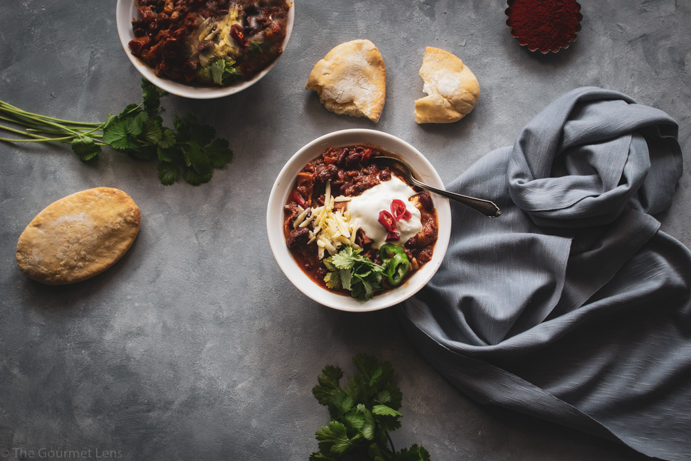 Flatlay photo of two bowls of chilli topped with sour cream and cheese and served with pitta and fresh coriander