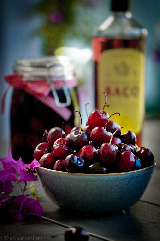 bowl of cherries with a bottle of brandy and jar of cherry brandy in the background