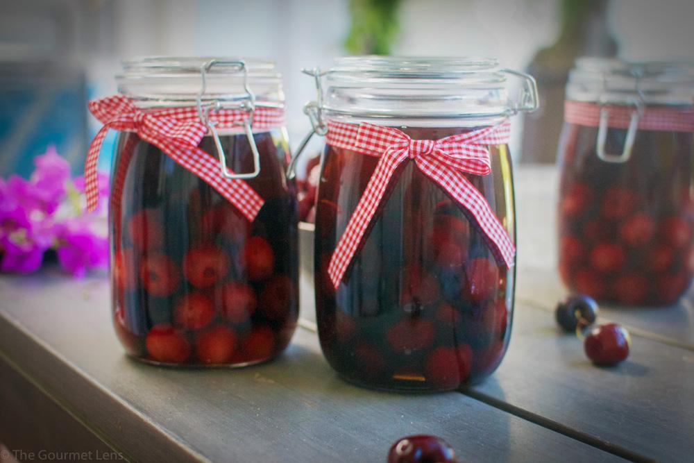 two jars of cherries marinating in brandy