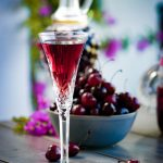 crystal glass with homemade cherry brandy with a bowl of cherries
