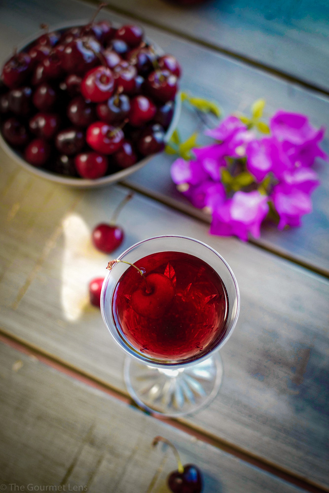flatly of cherry brandy on a crystal glass next to fresh cherries
