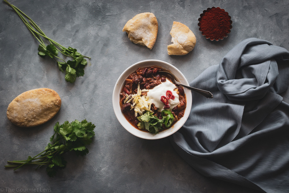 Flatlay photo of a bowl of chilli topped with sour cream and cheese and served with pitta and fresh coriander