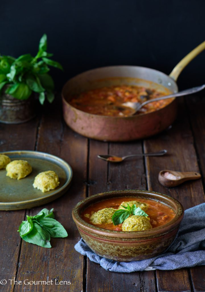 Lifestyle rustic scene of a bowl of Tuscan bean stew topped with herb dumplings with a big bunch of basil and a copper pot in the background