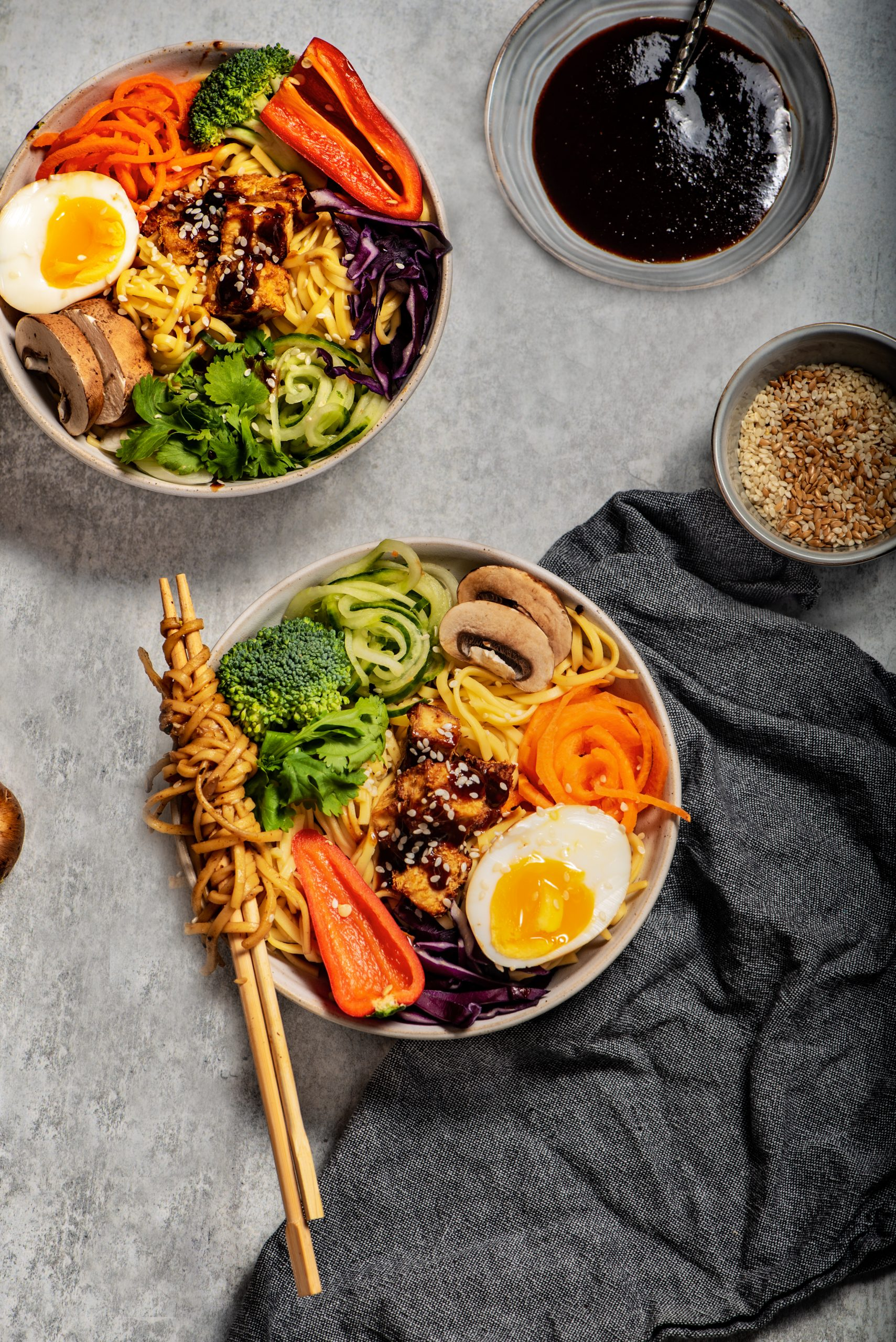 Flat lay of tofu noodle bowl with 2 bowls and spiralled vegetables and noodles twisted on a chopstick