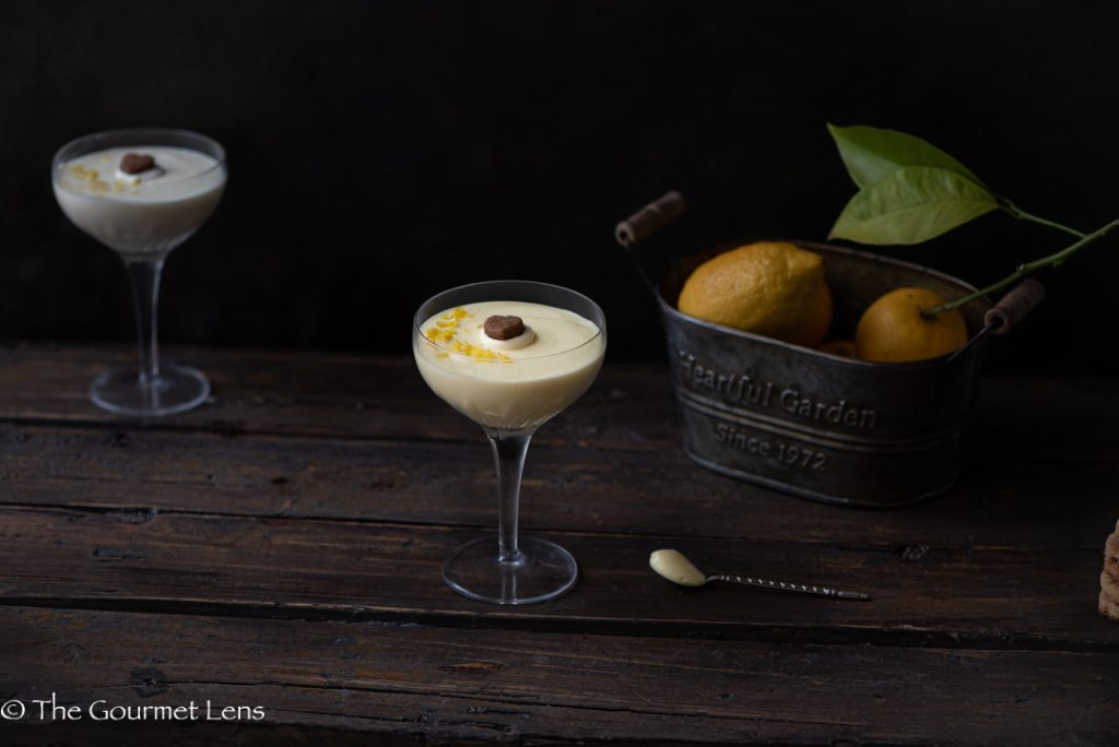 Dark and moody photo of lemon and ginger posset in an old fashioned champagne glass with lemons