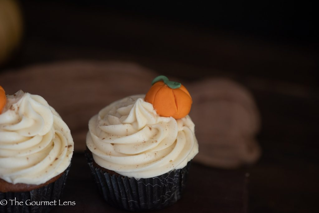 Macro shot of a cupcake swirl and an edible pumpkin