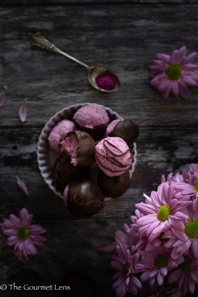 Flatlay of a bowl of pink pitaya coconut bliss balls with pink flowers