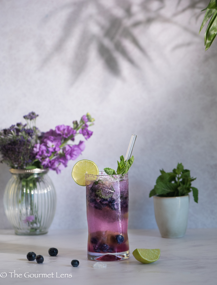 Blueberry mojito beside purple flowers with a palm tree reflection