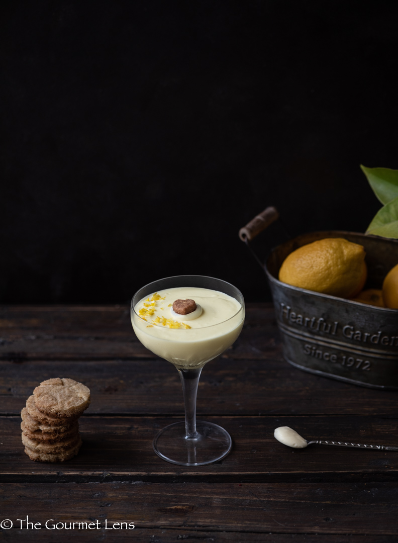 Dark and moody photo of lemon posset beside a stack of shortbread cookies and a rusty bowl of lemons