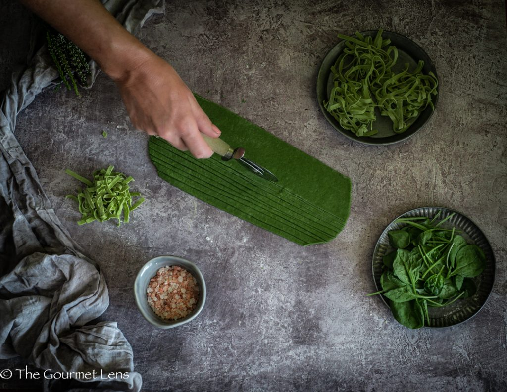 Cutting freshly rolled homemade spinach pasta with pizza roller