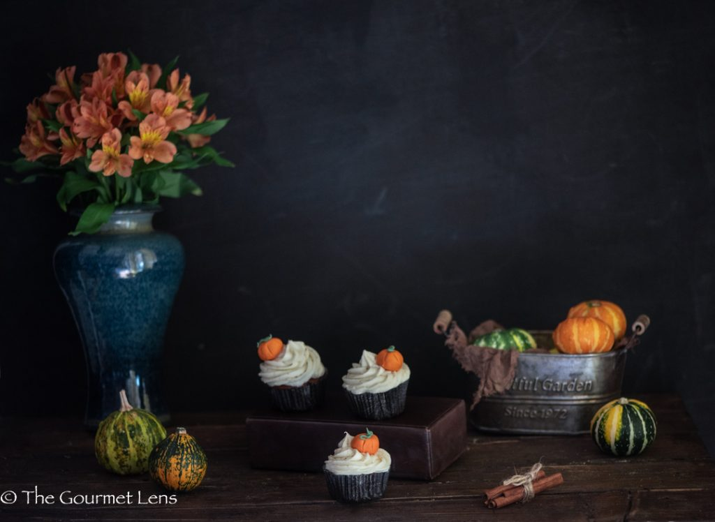 Dark and moody photograph of pumpkin spice cupcakes and maple frosting next to a basket of mini pumpkins