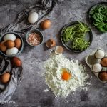 Flatlay of spinach pasta plus ingredients; flour, egg, salt and spinach