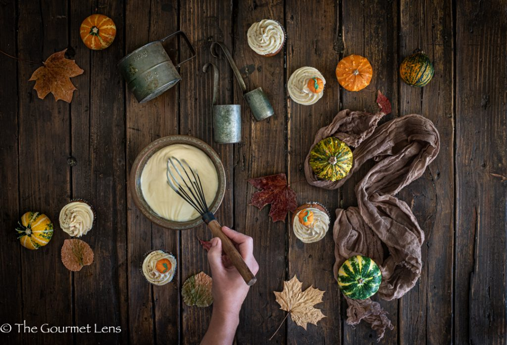 Flat lay photo of a hand whisking some frosting with mini pumpkins and cupcakes
