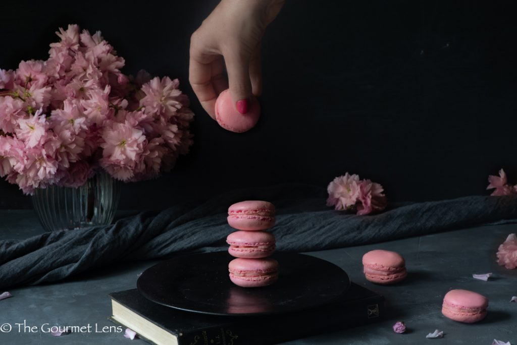 Hand reaching to grab a macaron from a black plate of pink macarons piled on top of each other with dark background