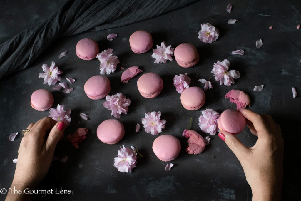 Flatlay of lots of pink macarons with cherry blossoms flowers and hands in photo