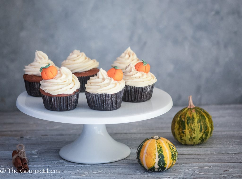 Close up of 6 pumpkin spice cupcakes with a maple frosting swirl and edible pumpkin