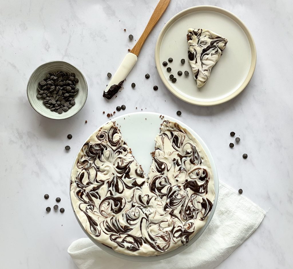 flatlay of Baileys Chocolate Swirl Cheesecake with a slice taken and melted chocolate and chocolate drops