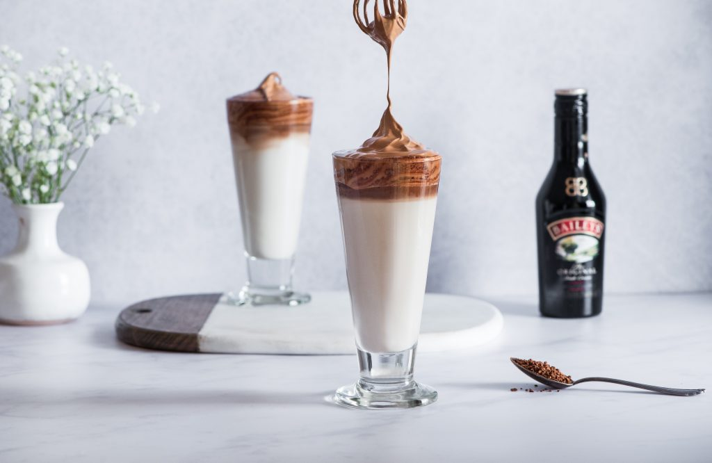 baileys daltons coffee being whisked with a bottle of baileys next to it