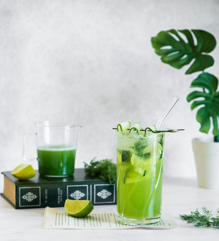 Cucumber and Dill Cocktail with a palm tree and pieces of lime scattered