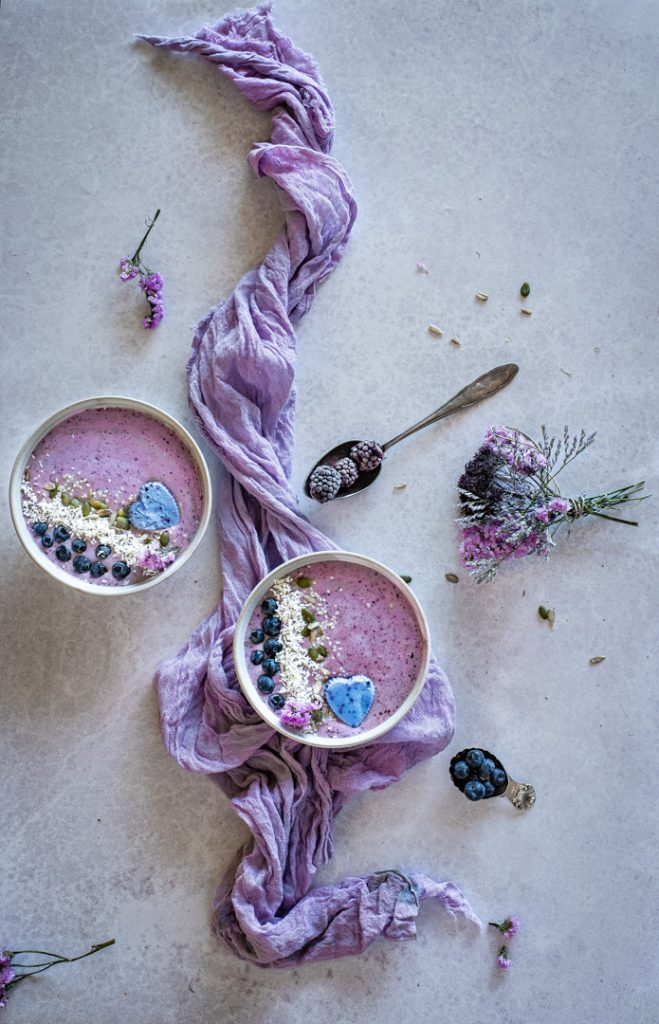 Overhead flatlay of açai berry smoothie bowls with purple linen and flowers