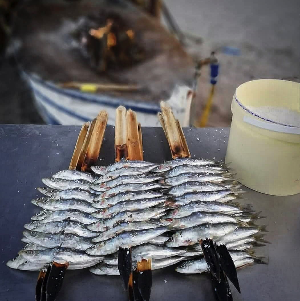 Wooden skewers of sardines ready to be barbecued on the beach