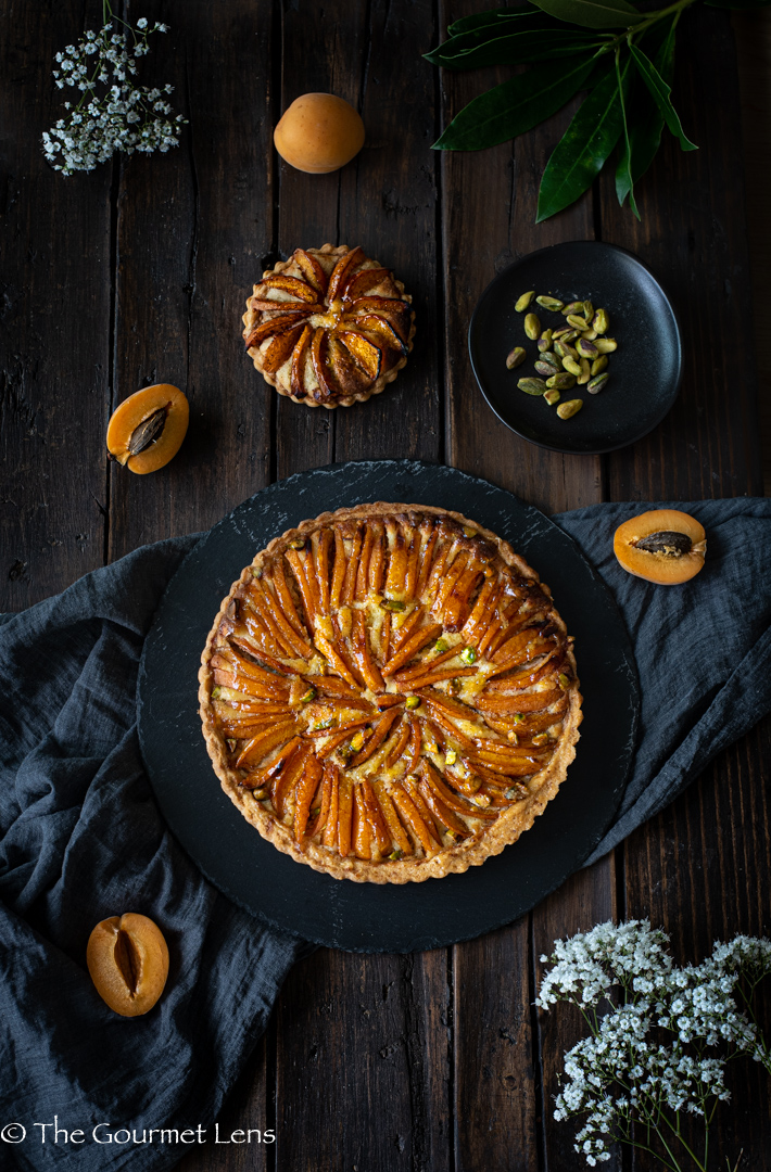 Flatlay of homebred apricot frangipane and cut fresh apricots on a dark wooden table