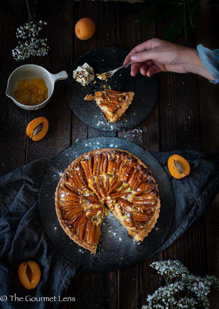 Overhead shot on a dark wooden background of a slice taken out of apricot frangipane tart and served with cream