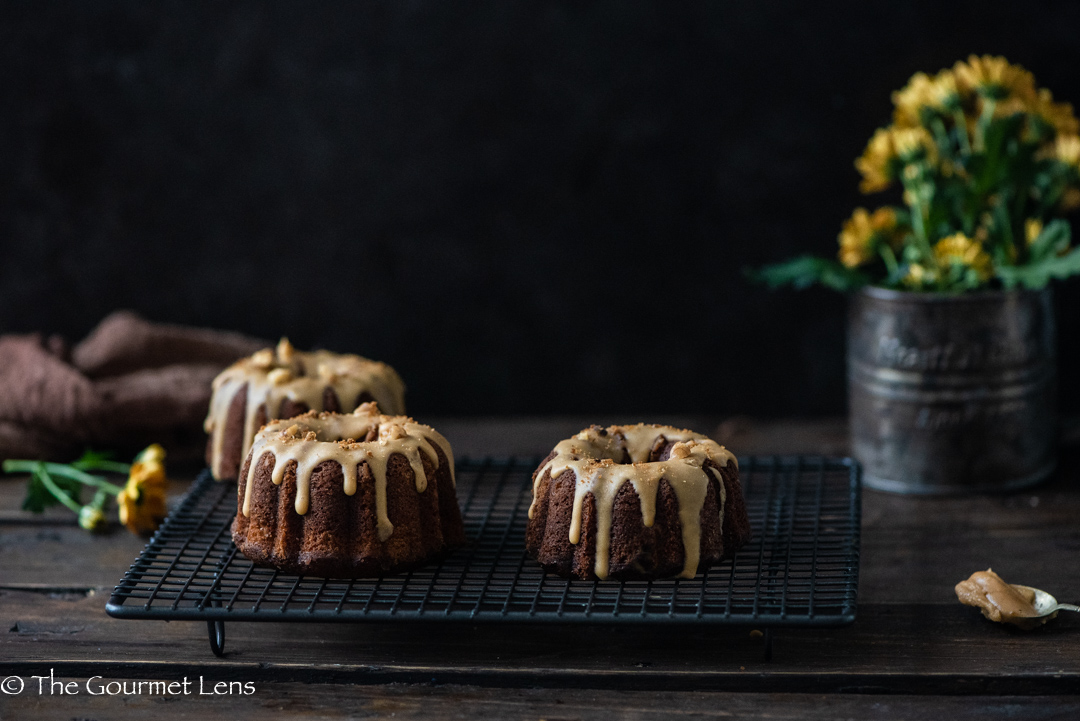 Mini coffee bundt cakes on a wired tray with drizzled icing and yellow flowers with a dark background