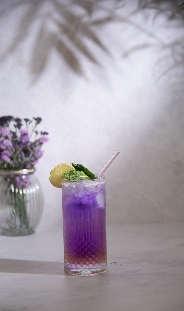 Glass of butterfly pea lemonade with some purple flowers and palm tree reflection