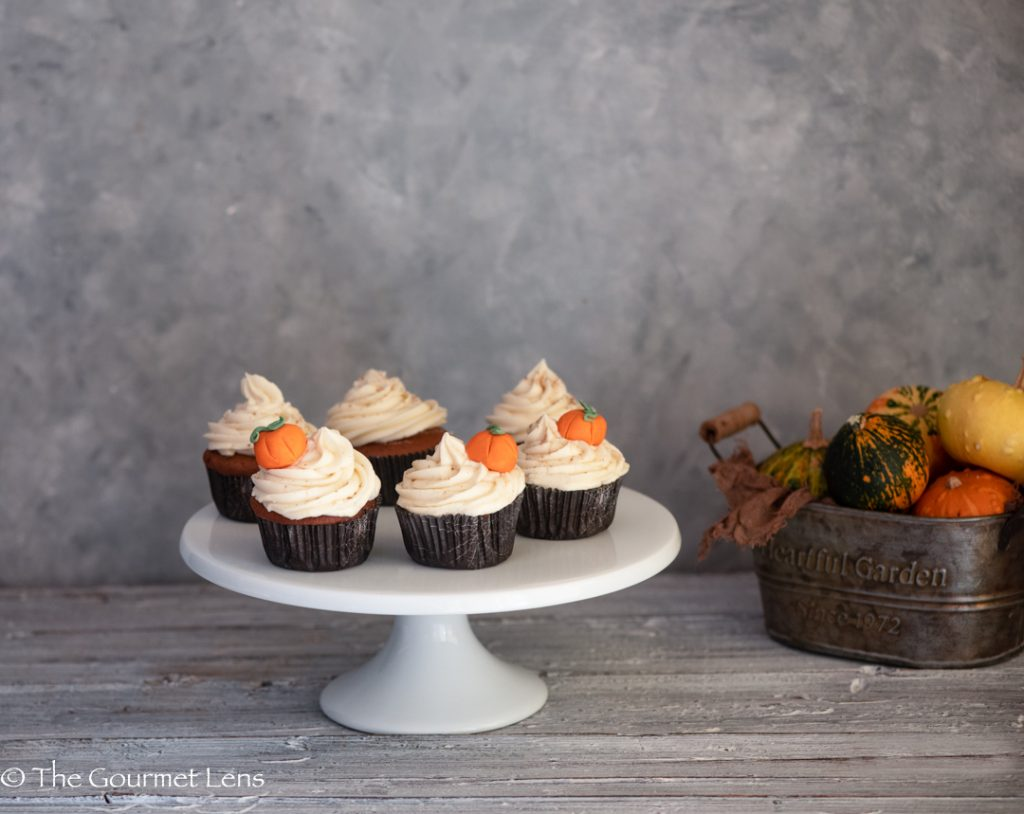 Cupcakes with maple frosting and edible pumpkin decorations